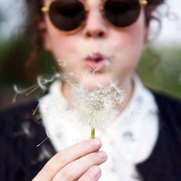 Girl blowing dandelion flower